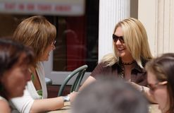 Two friends having a coffee break. Two friends at a pavement cafe in the summer sun stock photos