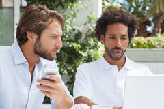 Two friends having coffee together with laptop Royalty Free Stock Images