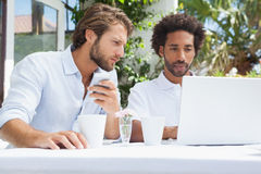 Two friends having coffee together with laptop Stock Photos