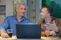 Two friends having drink and looking at laptop Stock Image