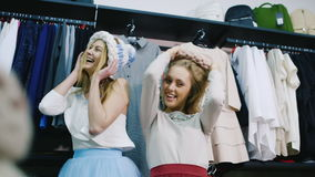 Two friends having fun in a clothing store. Try on hats and laughing, posing for the camera stock video footage