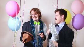 Two friends having fun dancing in photo booth. Two funny friends having fun dancing with props in party photo booth stock video