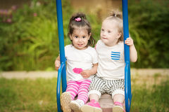 Two friends having fun ride on a  swing. Two friends having fun ride on a swing Royalty Free Stock Photo