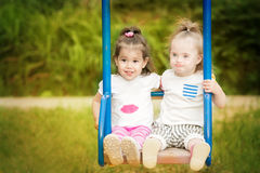 Two friends having fun ride on a  swing Stock Photos