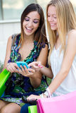 Two friends having fun with smartphones Stock Photography