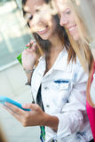 Two friends having fun with smartphones Stock Image