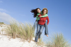 Two friends having piggy back at beach royalty free stock photo