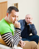 Two  friends having quarrel. Serious men sitting on sofa at home Stock Photography