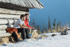 Two friends having rest on wooden bench in winter mountains outdoors. Two friends are having rest on wooden bench in winter mountains outdoors Stock Photo