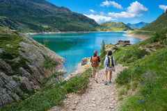 Two friends during a hike in the mountains walking near an alpine lake stock image