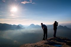 Two friends. Hiker thinking and photo enthusiast takes photos  stay on cliff. Dreamy fogy landscape, blue misty sunrise in a beaut Stock Images