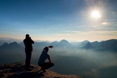 Two friends. Hiker thinking and photo enthusiast takes photos  stay on cliff. Dreamy fogy landscape, blue misty sunrise in a beaut Royalty Free Stock Photos