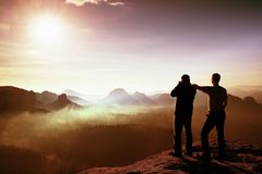 Two friends. Hiker thinking and photo enthusiast takes photos  stay on cliff. Dreamy fogy landscape, blue misty sunrise in a beaut Stock Photography