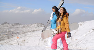 Two friends hiking up ski slope. Two smiling beautiful female friends in long black hair and snow suits hiking up white mountain slope with their snowboard and Royalty Free Stock Images