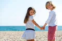 Two friends holding hands on beach. Stock Photos