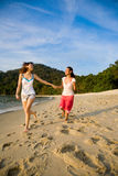 Two friends holding hands running along the beach Stock Image