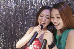 Two friends holding microphones and singing together at karaoke Stock Photo