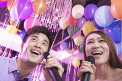 Two friends holding microphones and singing together at karaoke, balloons in the background Stock Photography