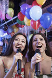 Two friends holding microphones and singing together at karaoke, balloons in the background Royalty Free Stock Photos
