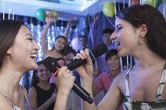 Two friends holding microphones and singing together at karaoke, face to face, friends in the background Royalty Free Stock Photography