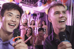 Two friends holding microphones and singing together at karaoke, friends in the background Royalty Free Stock Image