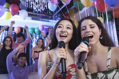 Two friends holding microphones and singing together at karaoke, friends in the background Stock Photos