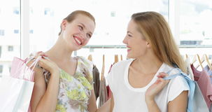 Two friends holding shopping bags smiling at camera. In a fashion boutique stock video footage