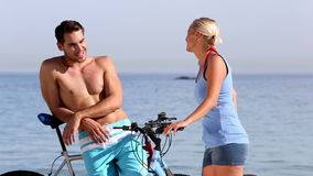 Two friends holding their bikes on the beach. Two friends holding their bikes and speaking on the beach stock footage
