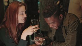 Evening people interactions in bar. Two friends or interracial couple, caucassian woman and afro american man meet for date at romantic bar or restaurant, drink stock footage