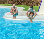 Two  friends jumping in the pool Royalty Free Stock Photography