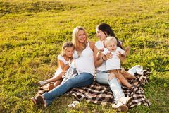 Two friends with kids laughing outdoors. Two young women with kids enjoying sunshine in park. Beautiful pregnant women with her friend and their kids. Mother's Royalty Free Stock Photography