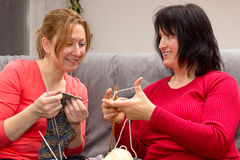 Two friends knitting together Stock Photos