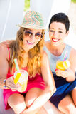 Two friends at lake beach relaxing with drinks Royalty Free Stock Image