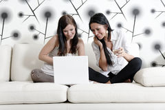 Two friends on a laptop at home Stock Image