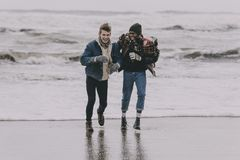 Friends Having Fun On A Winter Beach. Two friends laughing and having fun on a winter beach royalty free stock photography