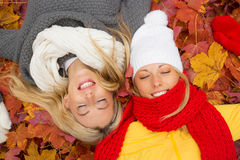 Two friends laying in leafs with closed eyes Stock Photo