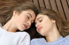Two friends lie on a bench leaning their heads against each othe. R. They have long brown hair and clean skin Stock Photos