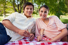Two friends lie down on a blanket while holding champagne Stock Photos