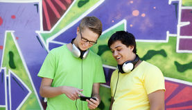 Two friends listening music near graffiti wall. Royalty Free Stock Photos