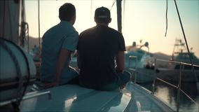 Two friends looking at the bay with yachts on a sunset. Slow motion stock video footage