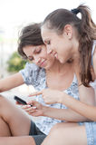 Two friends looking at cellphone Stock Images