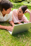 Two friends looking at each other as they use a laptop together. Two friends smiling while looking at each other as they use a laptop together on the grass Royalty Free Stock Image