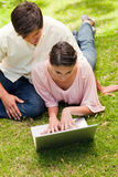 Two friends looking into a laptop together. While lying down in the park Stock Image