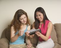 Two friends looking at photos. Two friends at home looking at photographs Royalty Free Stock Photos
