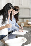 Two friends looking at recipes Royalty Free Stock Photo