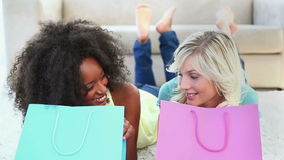 Two friends looking into shopping bags. While lying on a carpet stock video footage