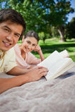Two friends looking to the side while reading in a park Royalty Free Stock Images