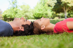 Two friends looking upwards while lying head to head Stock Photo