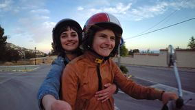 Two friends or lovers ride vintage scooter. Action camera shot of two happy and excited young women students blonde and brunette riding vintage scooter in retro stock video footage