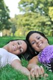 Two friends lying outdoors in grass holding hands Royalty Free Stock Photo
